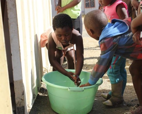 Children washing their hands before their meal, Freedom Park, South Africa