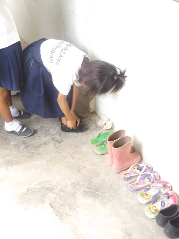 Badjao children being respectful of their uniforms before class