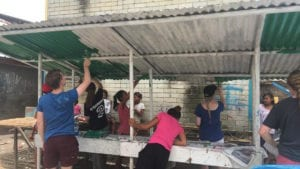 SERVE volunteers and Badjao vendor owners refurbishing the stalls together